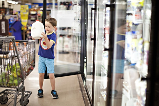kid grocery shopping with gallon of milk