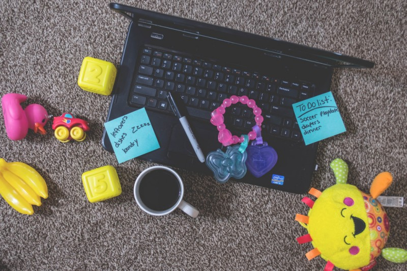 laptop with baby toys scattered around it