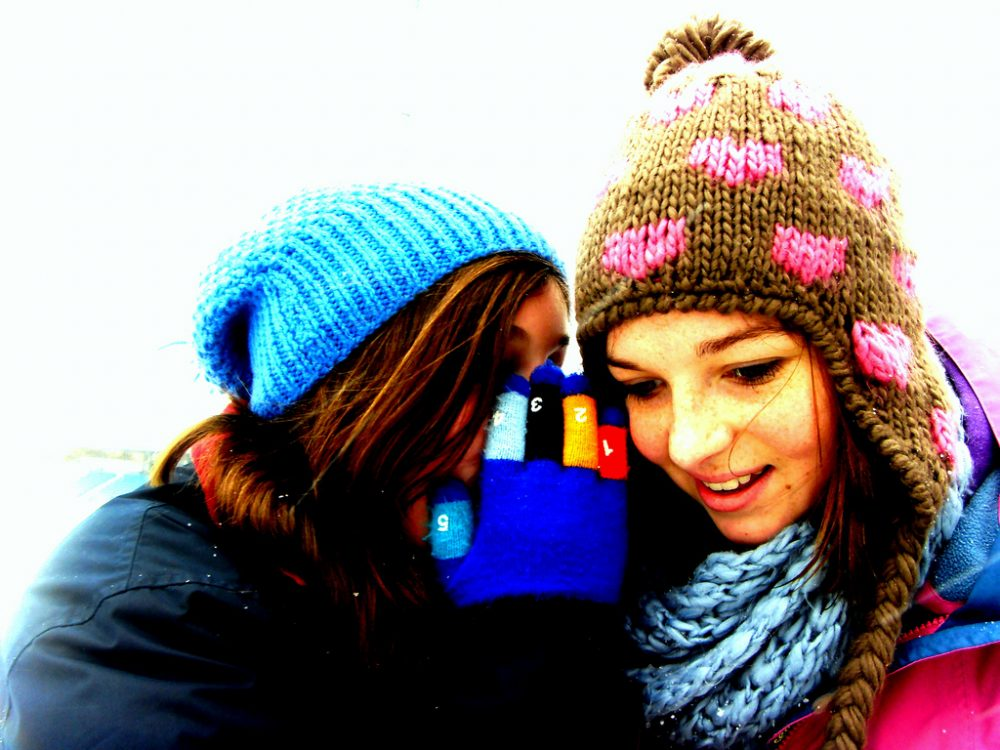 two friends whispering - what your credit score says about you