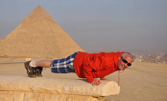 Man doing push-ups in front of pyramids