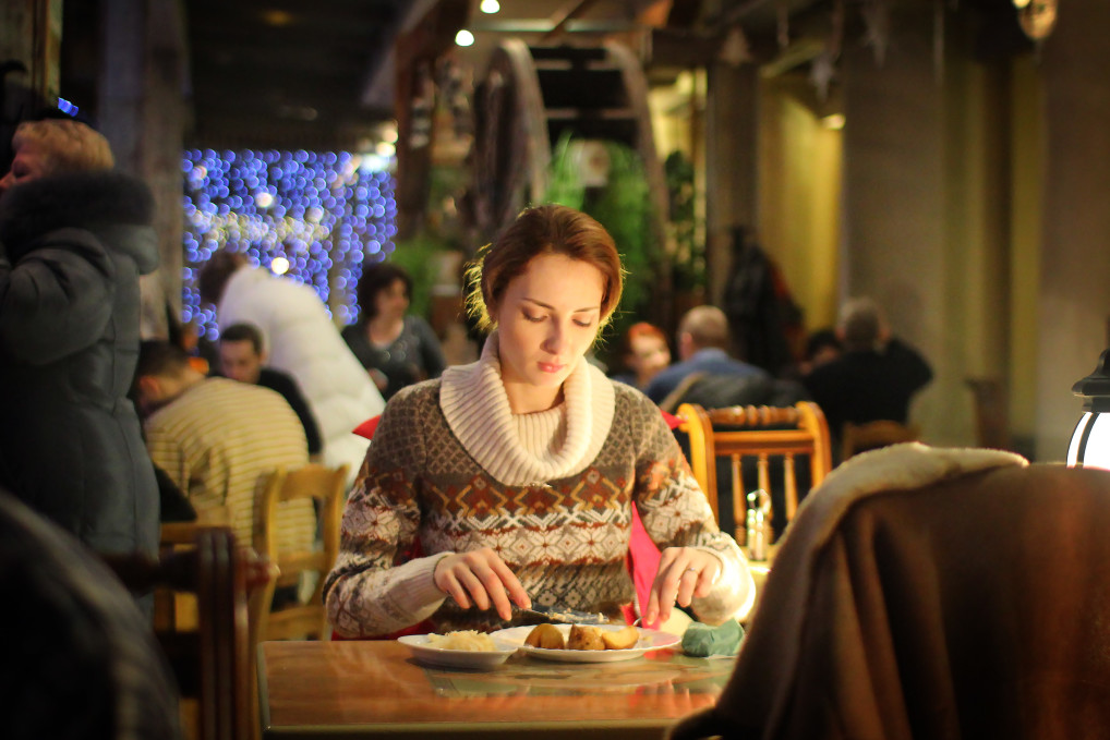 single woman eating at restaurant alone